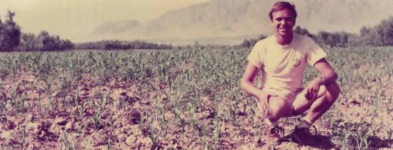 Ben dronkers hockende und lächelnd für ein Foto auf einem Gebiet der Kulturpflanzen in Afghanistan