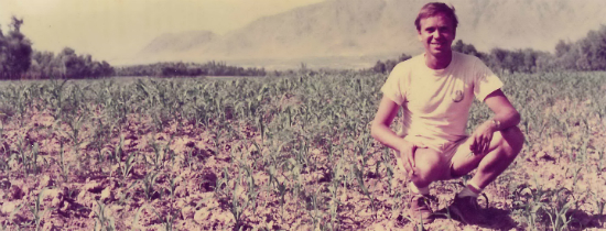 Ben Dronkers crouching and smiling for a photo in a field of crops in Afghanistan
