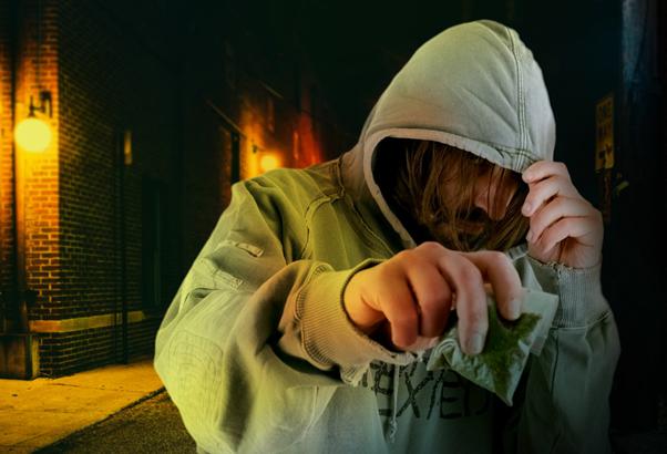 Een man die een kap draagt die laag over zijn gezicht heeft getrokken, houdt een zak cannabis vast