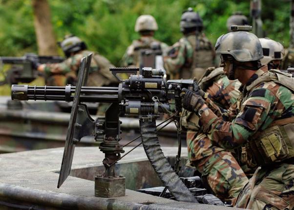 Een soldaat met camouflage en een helm die een groot machinegeweer richt