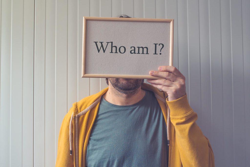 """Een man met een teken voor zijn gezicht, wat zegt: """"Wie ben ik?"""
