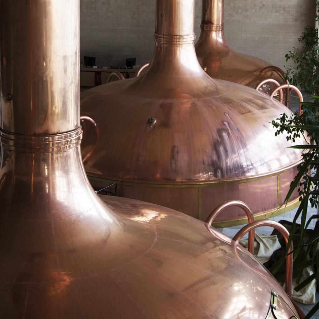 Tres teteras de cobre grandes dentro de una cervecería.