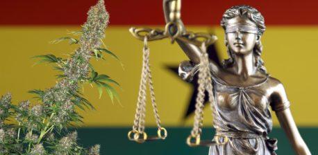 Die ghanische Flagge, eine Statue einer Frau, die ausbalancierte Waagen und eine Cannabis-Pflanze hält