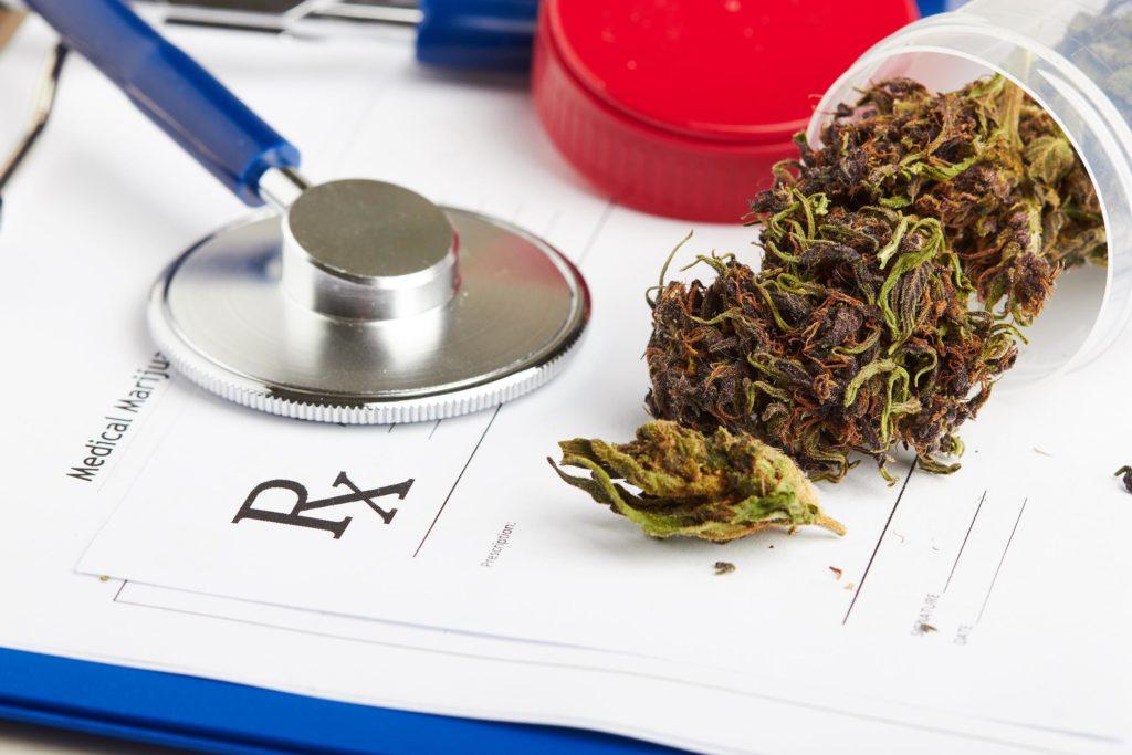 Cannabisknoppen in een plastic container, een medische vorm en een stethoscoop