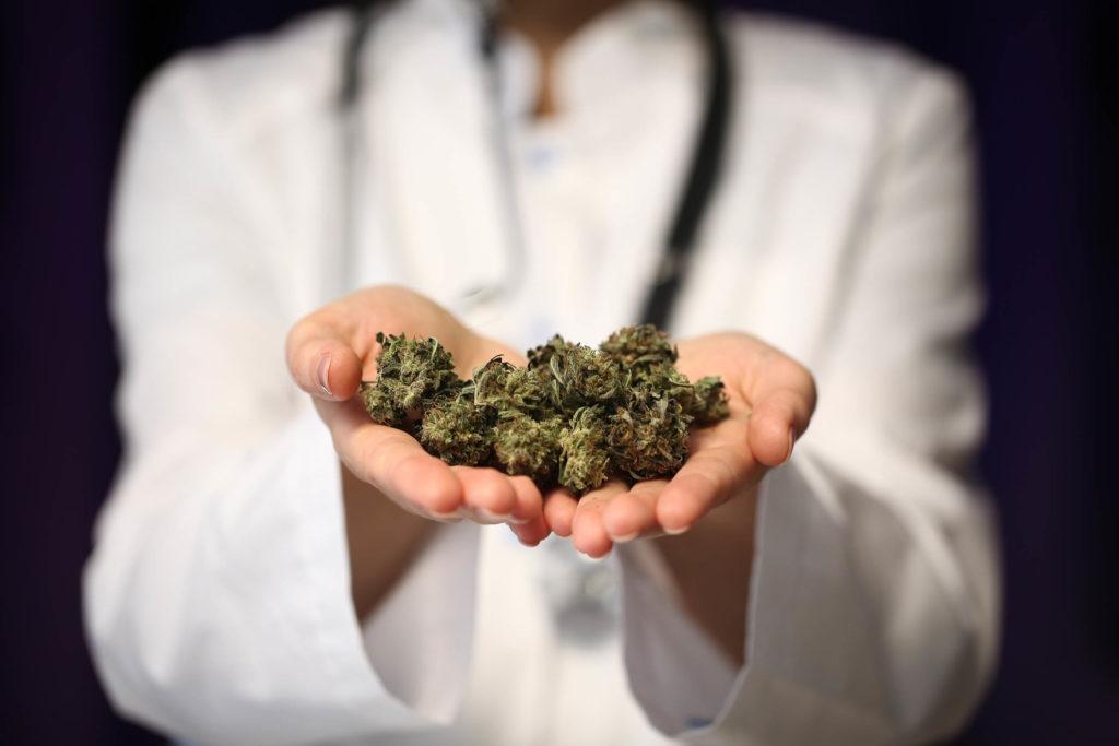 Ein Arzt mit einem Stethoskop um seinen Hals, der Cannabis hält