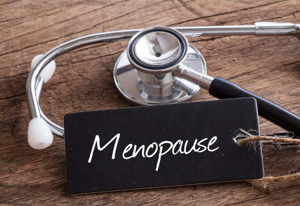 """Un estetoscopio y una etiqueta negra con la palabra """"menopausia""""."""