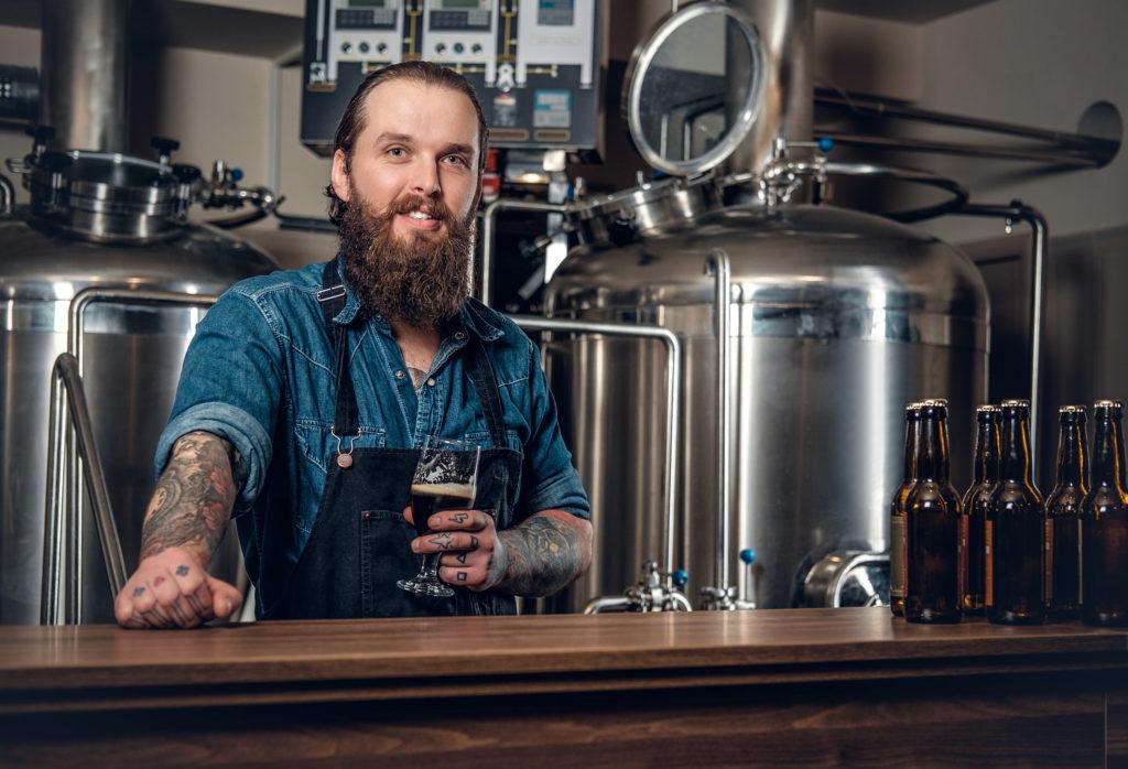 Un barman vistiendo un delantal y sosteniendo un vaso de cerveza.