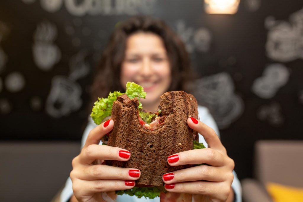 A woman holding a whole wheat bread sandwich