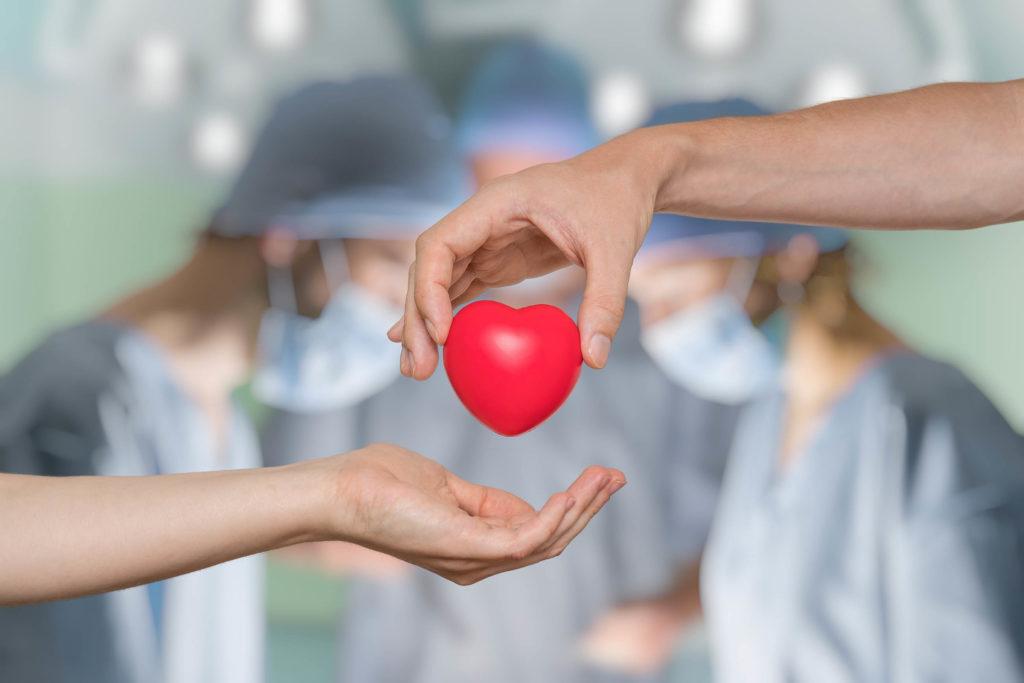 Alguien pasa un corazón rojo a otra persona. En el fondo hay tres cirujanos.