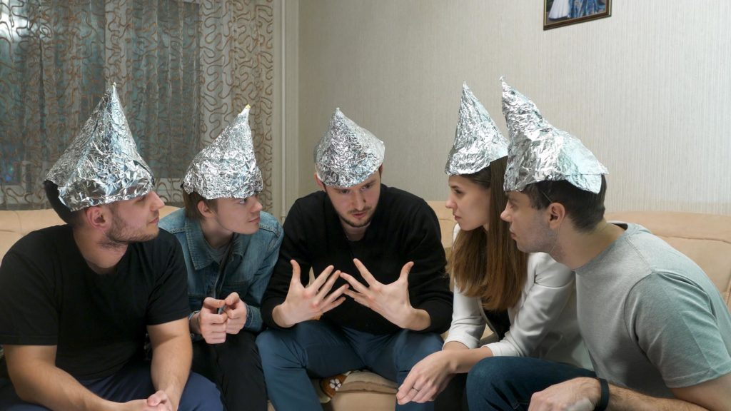 People sitting on a couch and talking with aluminium foil hats