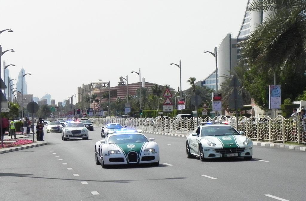 Eine Reihe von Polizeiautos, die eine Hauptstraße hinunterfahren