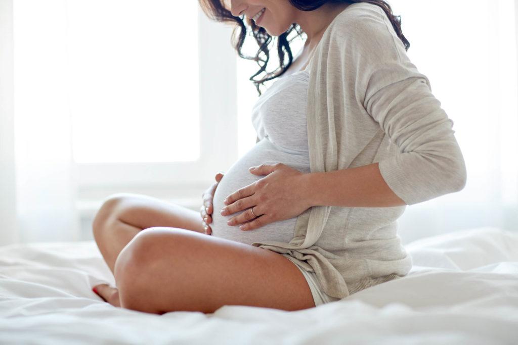 Une femme enceinte assise sur le lit qui tient son ventre
