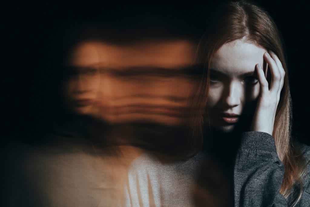 Een vrouw die haar hand aan haar hoofd houdt. Er is een wazig vrouw in dubbele visie.