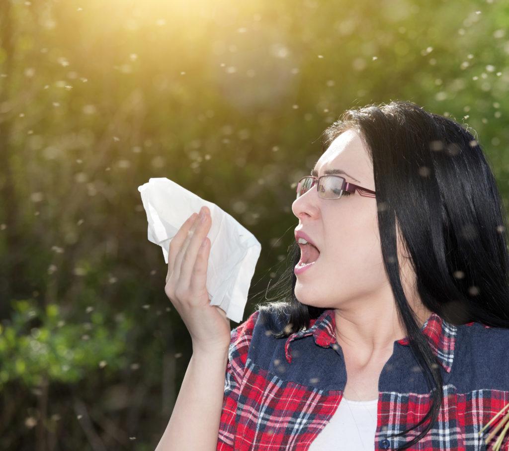 Eine Frau, die draußen steht und in ein Gewebe niest