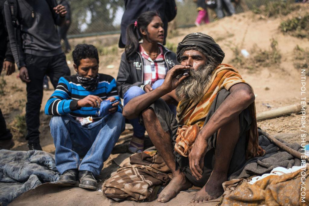 Tres residentes nepaleses se sentaron en las articulaciones de la arena fumando.