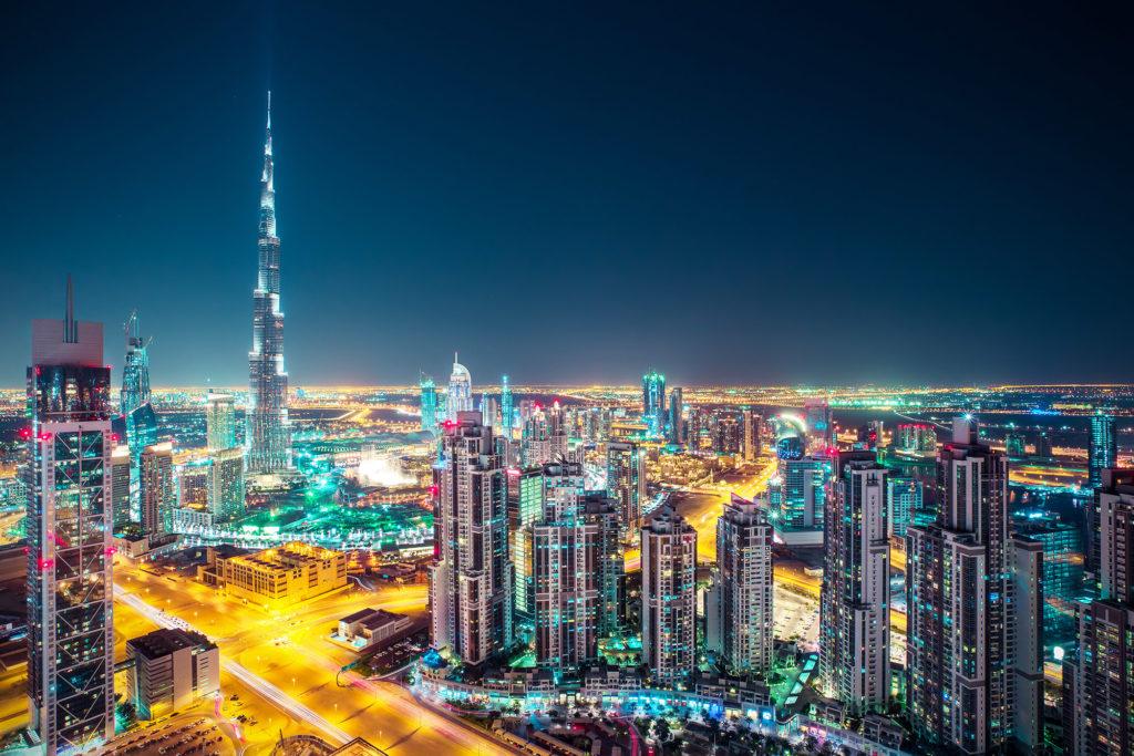 Ein Stadtbild von Dubai nachts mit hellen Lichtern