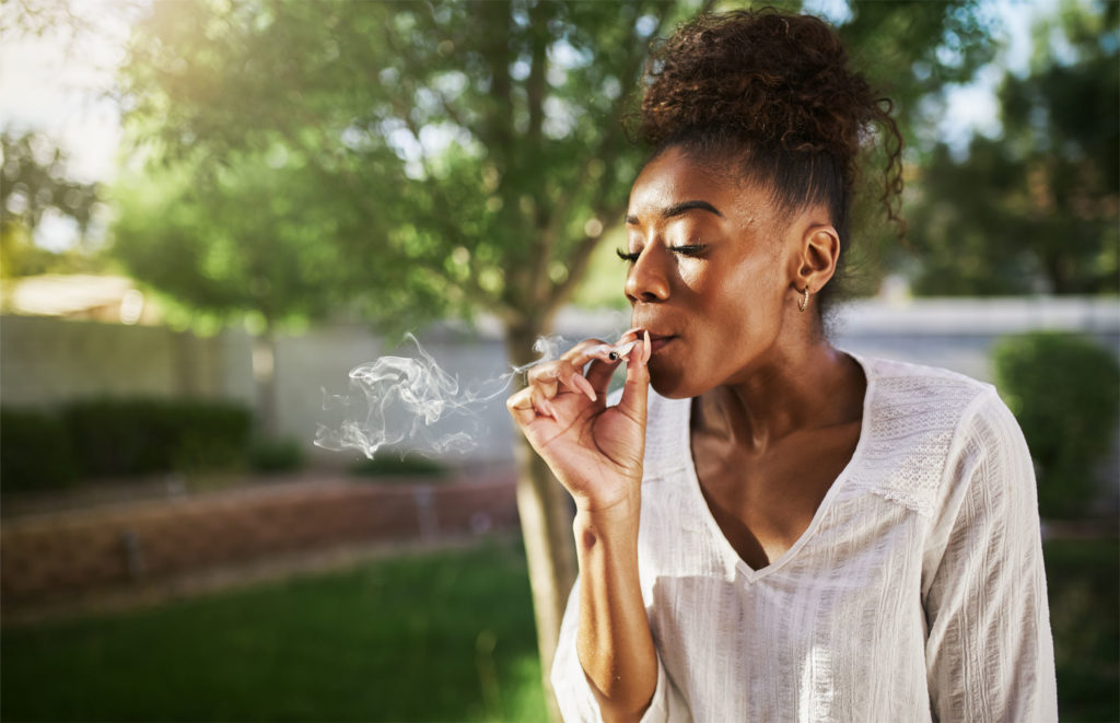 An African-American woman smoking a joint
