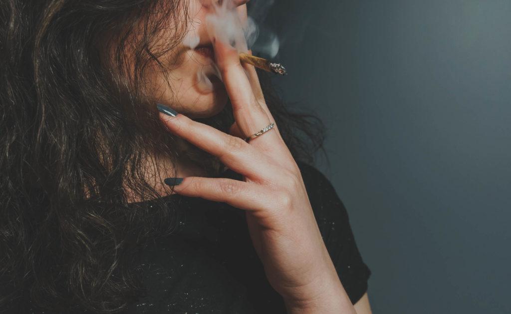Une femme aux cheveux bruns fumant une articulation
