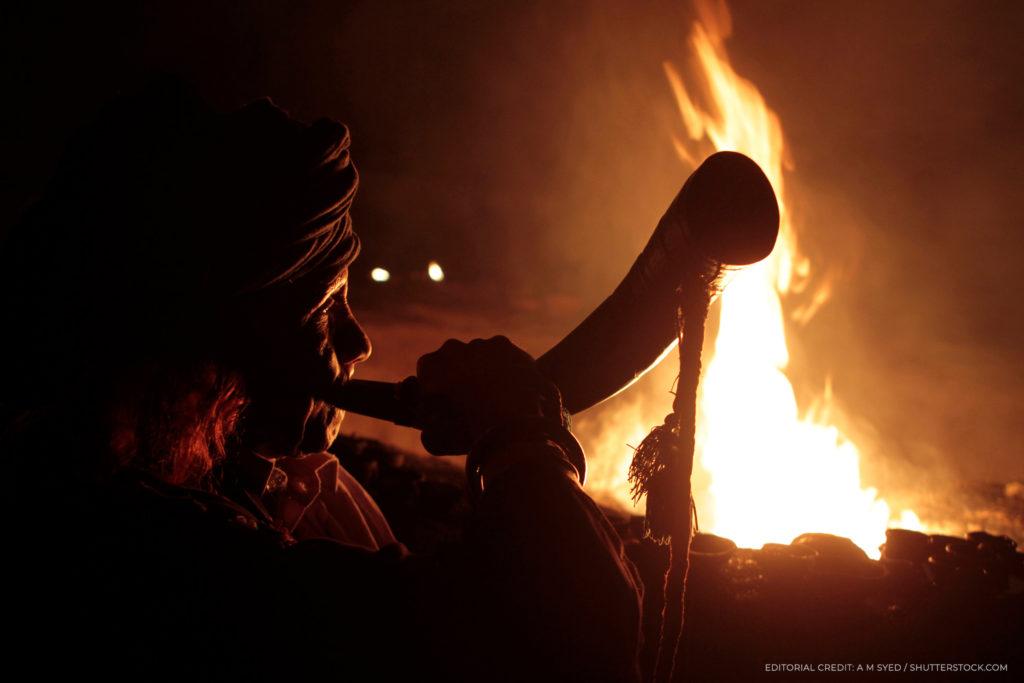 Une personne soufflant une corne devant un feu de camp