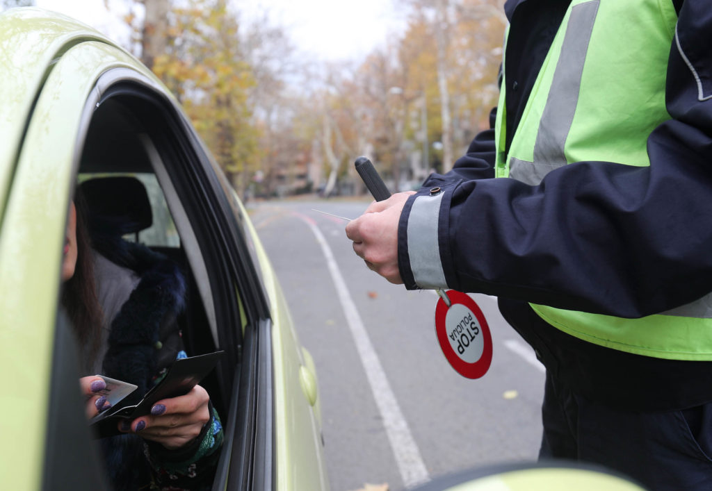 A policeman standing next to the window of a car talking to the driver