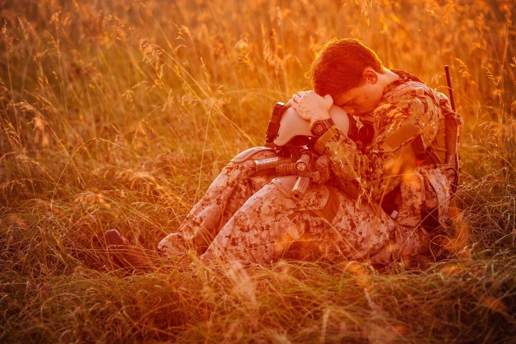 Een soldaat zat op een veld en rustte zijn hoofd op zijn helm
