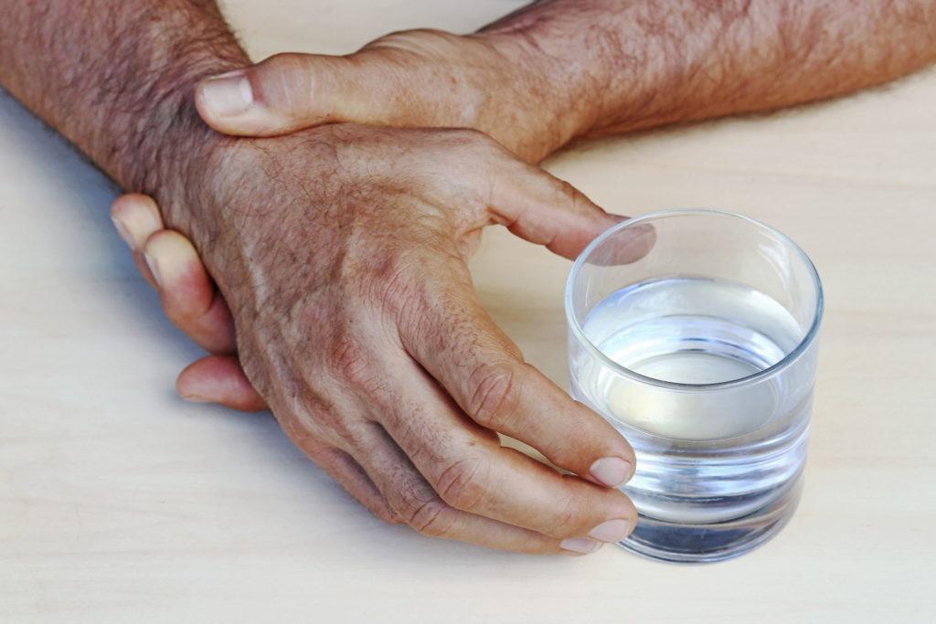 Een hand die naar een glas water bereikt. De andere hand houdt de tegenoverliggende pols vast