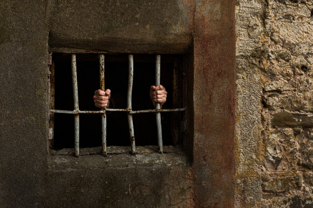 A person in a jail holding the bars of the cell