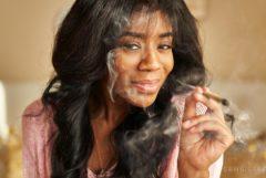 Eine afroamerikanische Frau, die ein beleuchtetes Gelenk lächelt und raucht