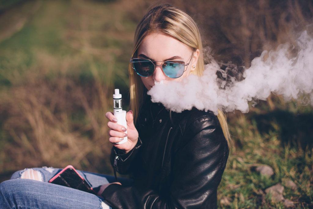 Une femme aux lunettes de soleil fumant E-liquide de vaporisateur