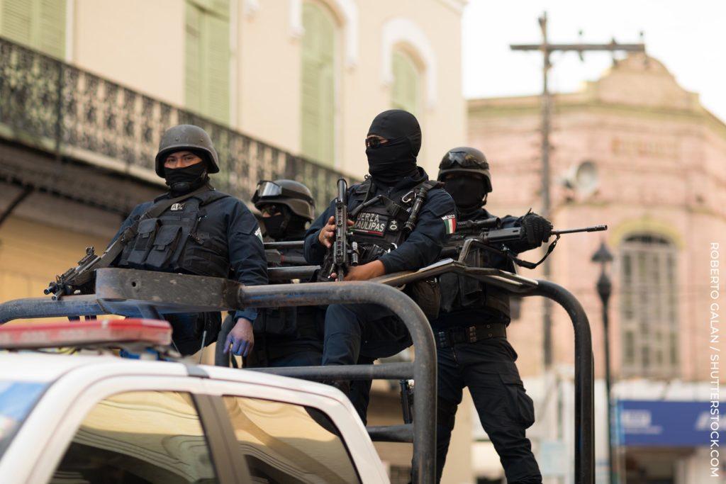 Cuatro hombres en equipo militar con pistolas