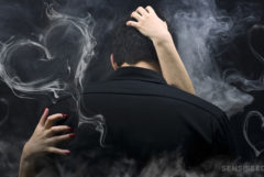 Two people kissing surrounded by smoke which has formed hearts
