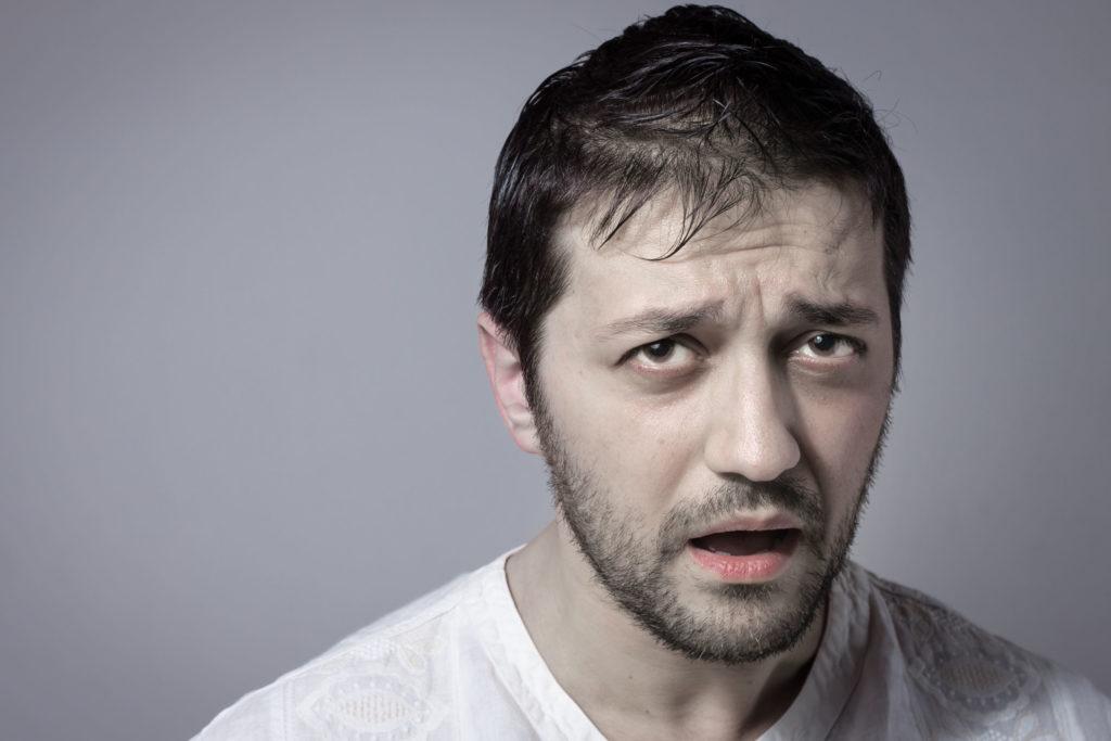 Een man die bleek en bezorgd kijkt. Hij is fronsen en zijn mond is open
