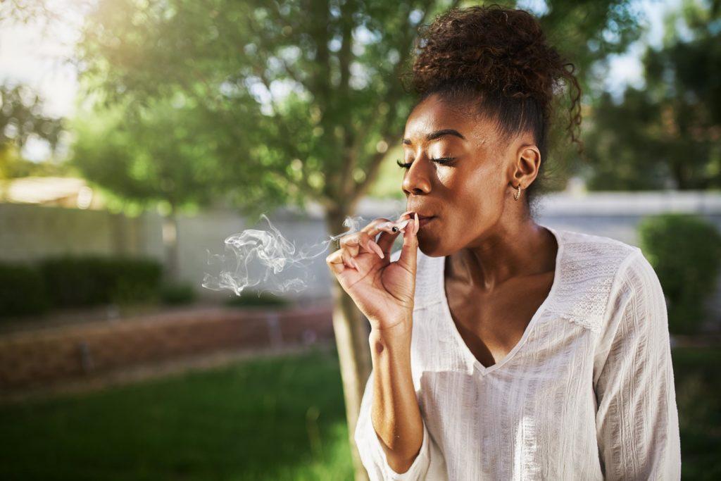 Une femme afro-américaine fumant une articulation