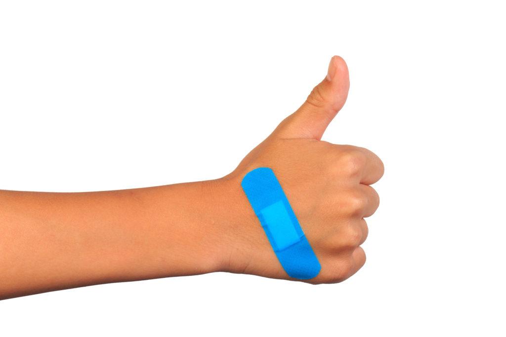 Une personne tenant le pouce avec un patch bleu