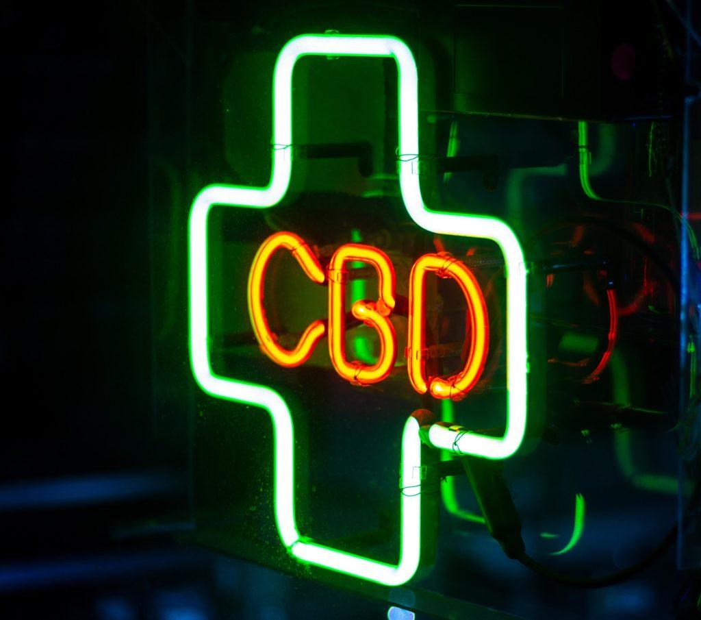 Een groen neon plus-teken met CBD in het midden in rood