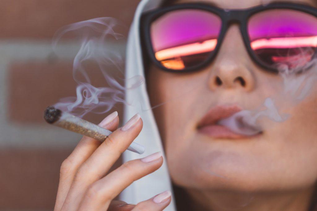Eine Frau, die Sonnenbrille trägt und ein Gelenk raucht
