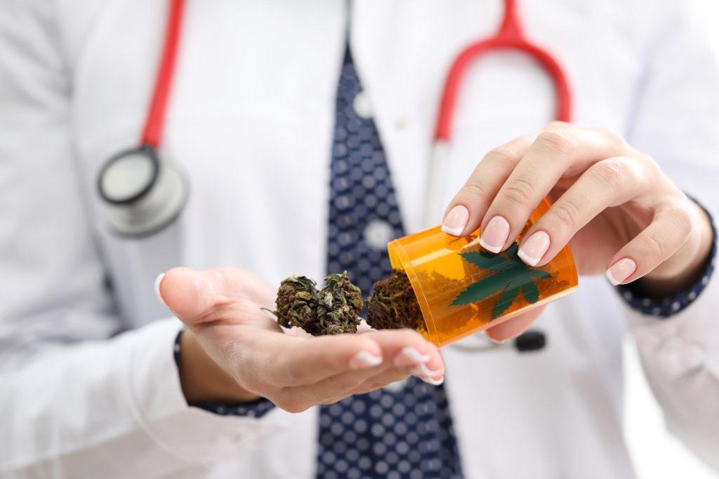 Eine Person mit dem Stethoskop, das medizinische Cannabis und einen medizinischen Behälter hält