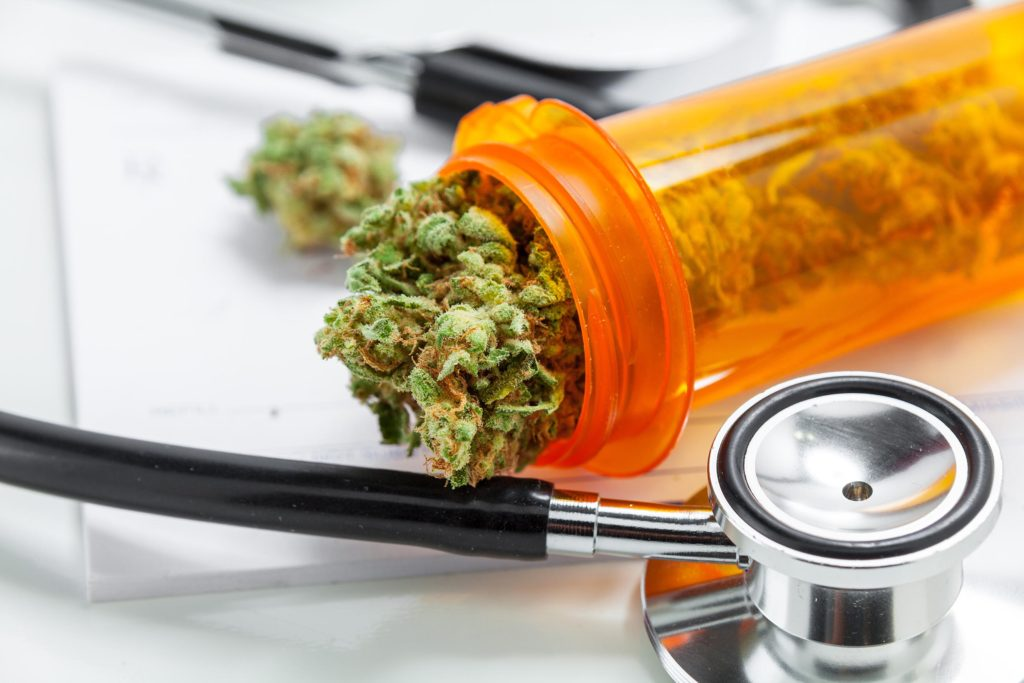 An orange tube of cannabis buds and a stethoscope