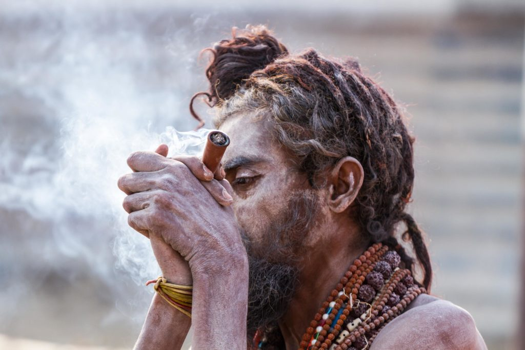 A person blowing smoke into their hands