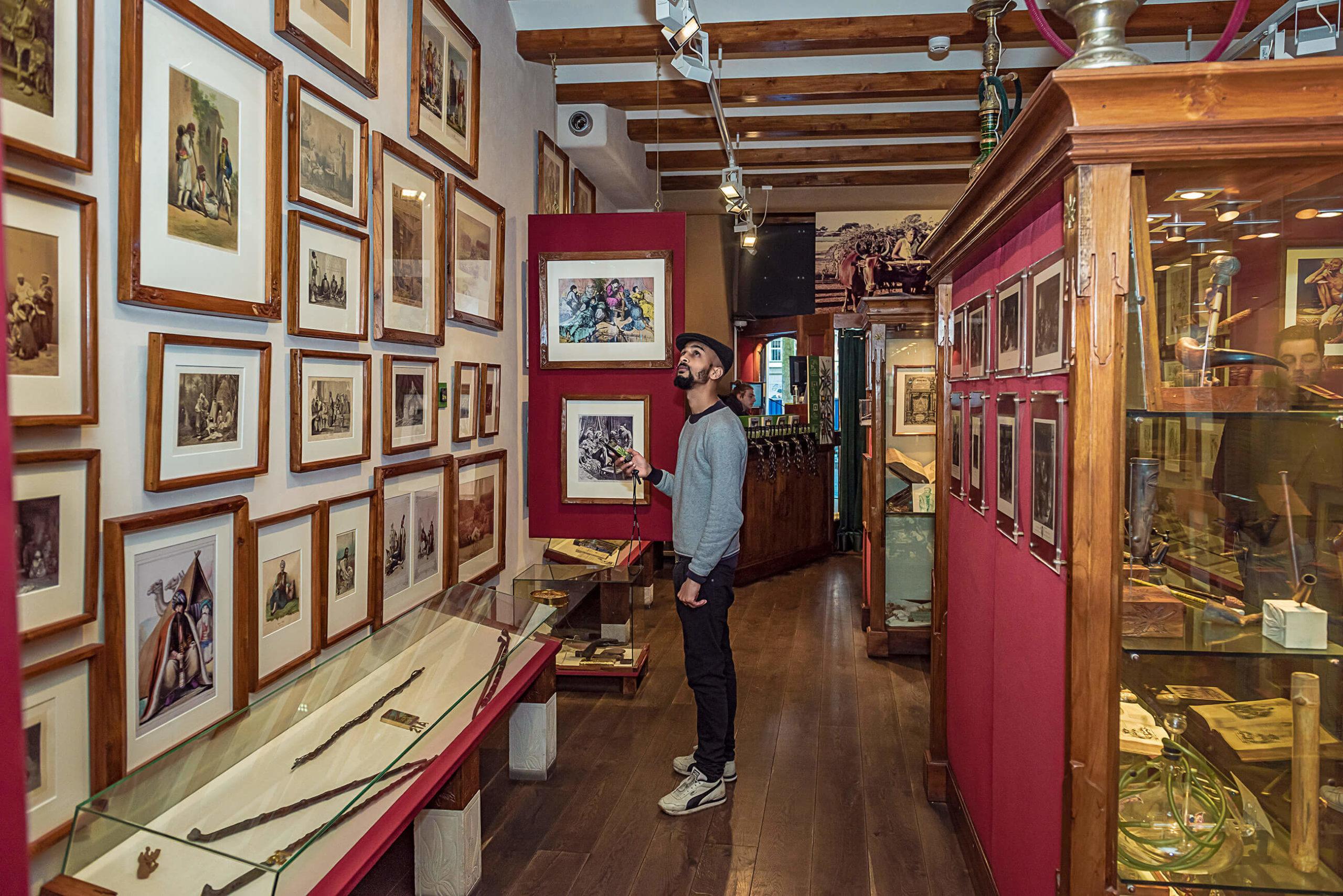 Un homme en regardant des images encadrées sur le mur à l'intérieur du musée