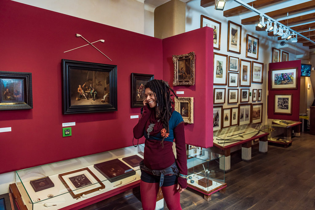 A woman with dreadlocks smiling on the phone as she walks through the museum