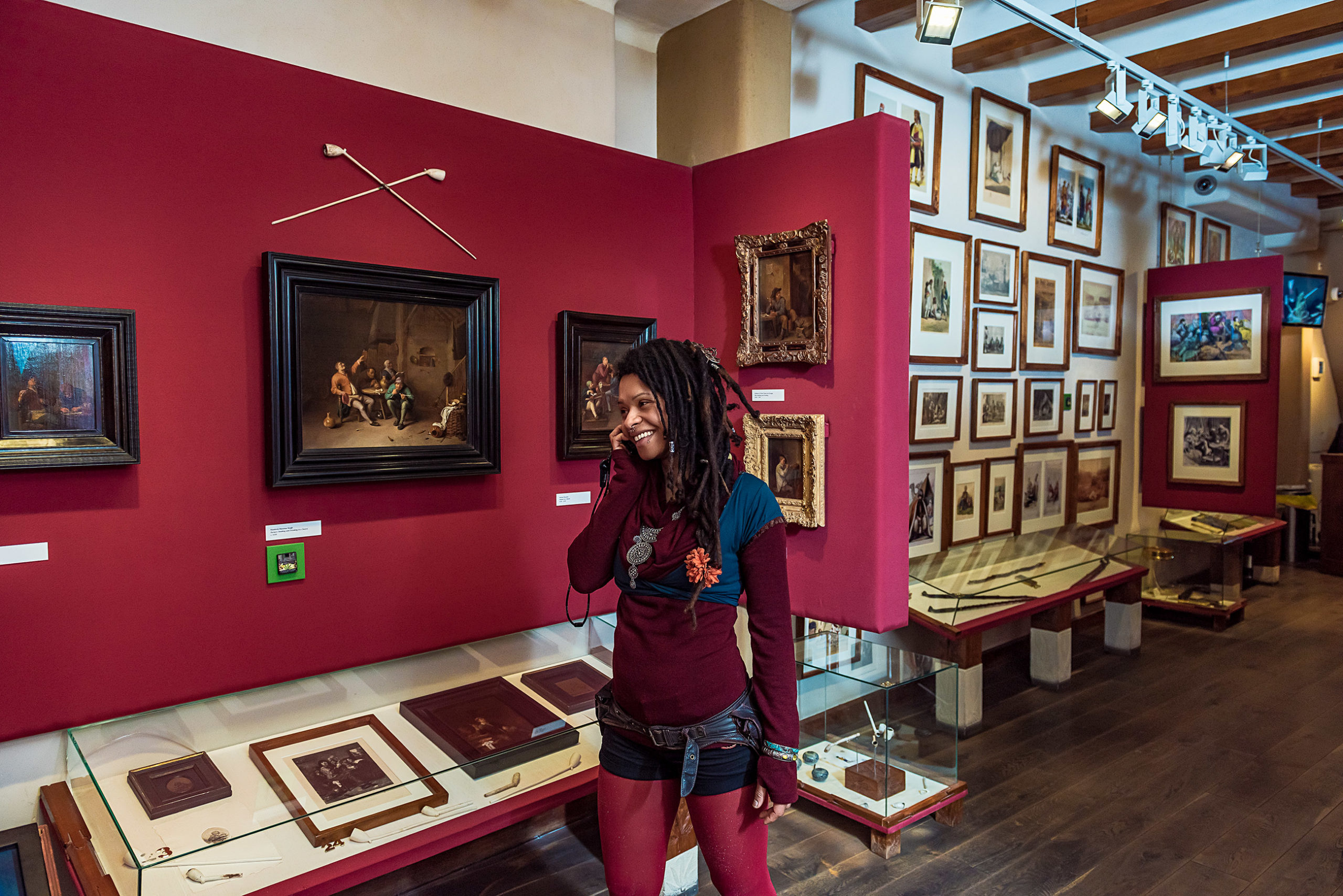 Une femme avec des dreadlocks souriant au téléphone alors qu'elle traverse le musée