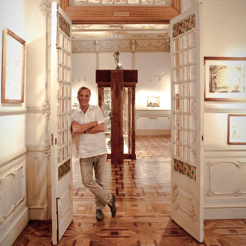 Un hombre con los brazos cruzados apoyados contra una puerta abierta.