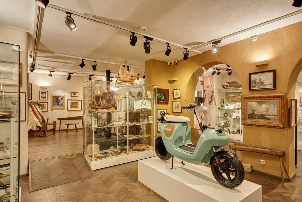 A light blue moped on display with glass cabinets and framed pictures in the background
