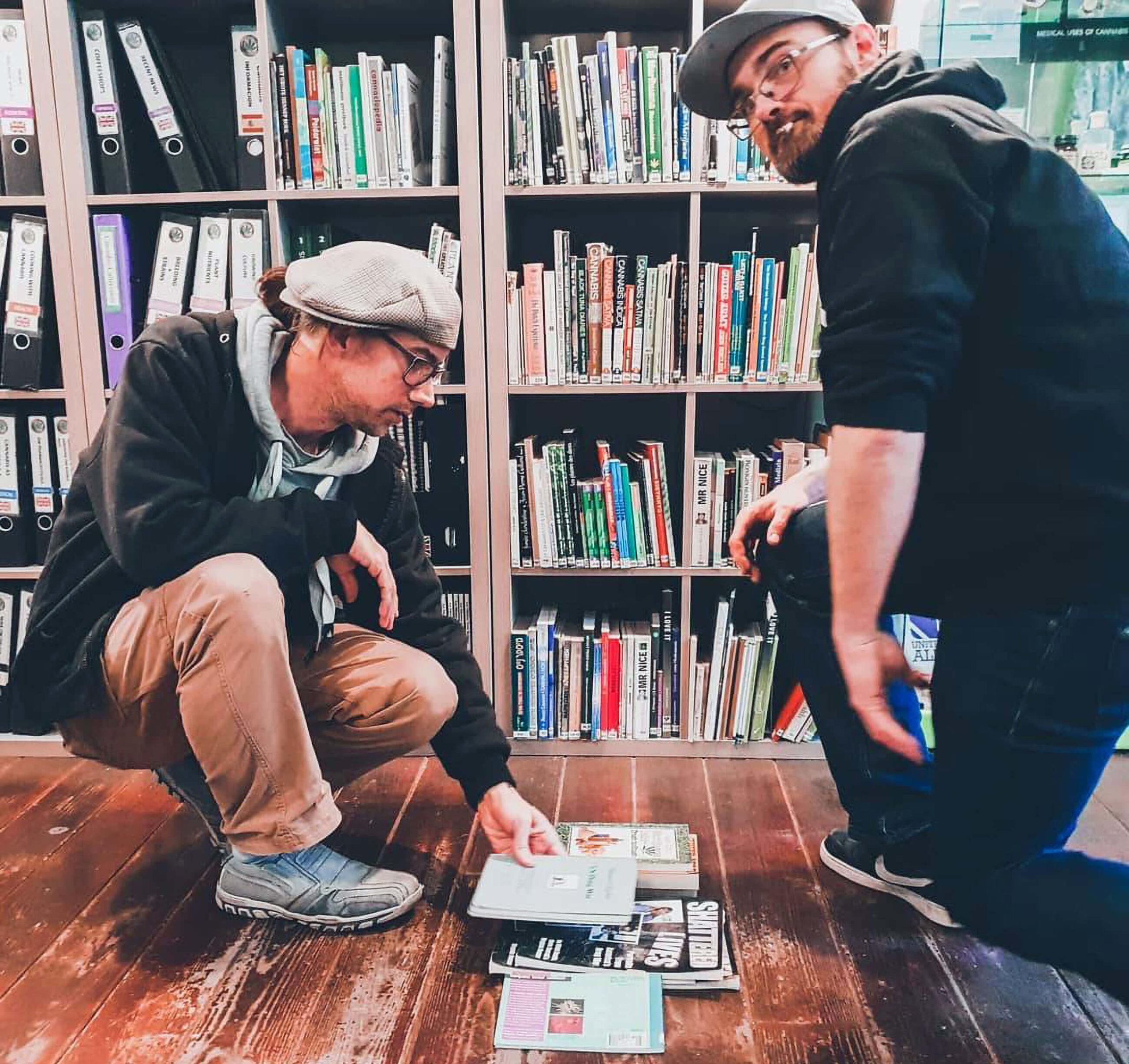 Zwei Männer, die verschiedene Bücher vom Cannabis College betrachten