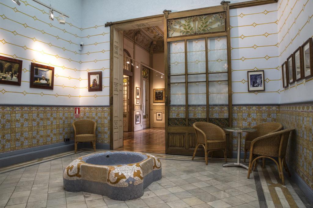 Ein Zimmer voller Bilder mit einem Brunnen in der Mitte, einem Tisch und ein paar Stühle
