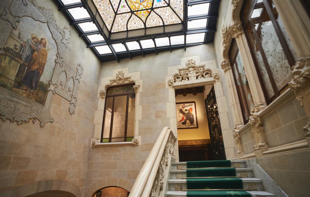 Una escalera con una alfombra verde en el edificio Palacio Mornau.