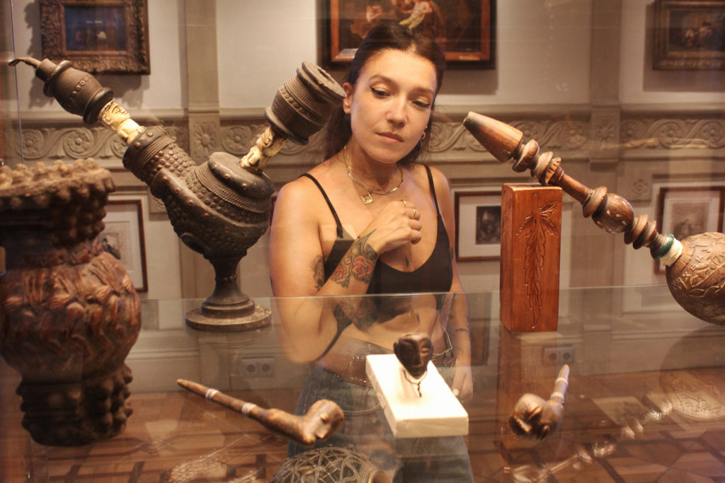 A woman looking at different historical artifacts related to cannabis on display in a cabinet