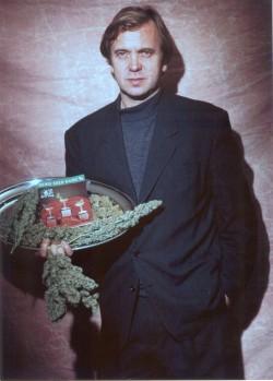 Ben Dronkers sosteniendo una bandeja de plata que muestra un catálogo de banco de semillas Sensi y hojas de cannabis